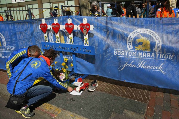 Joel (left) and Jackie Dalton leave mementos for Martin Richard, one of the victims of the 2013 Boston Marathon bombings, at a memorial for all the victims at the site of the first bomb blast in Boston on April 20, 2014.
