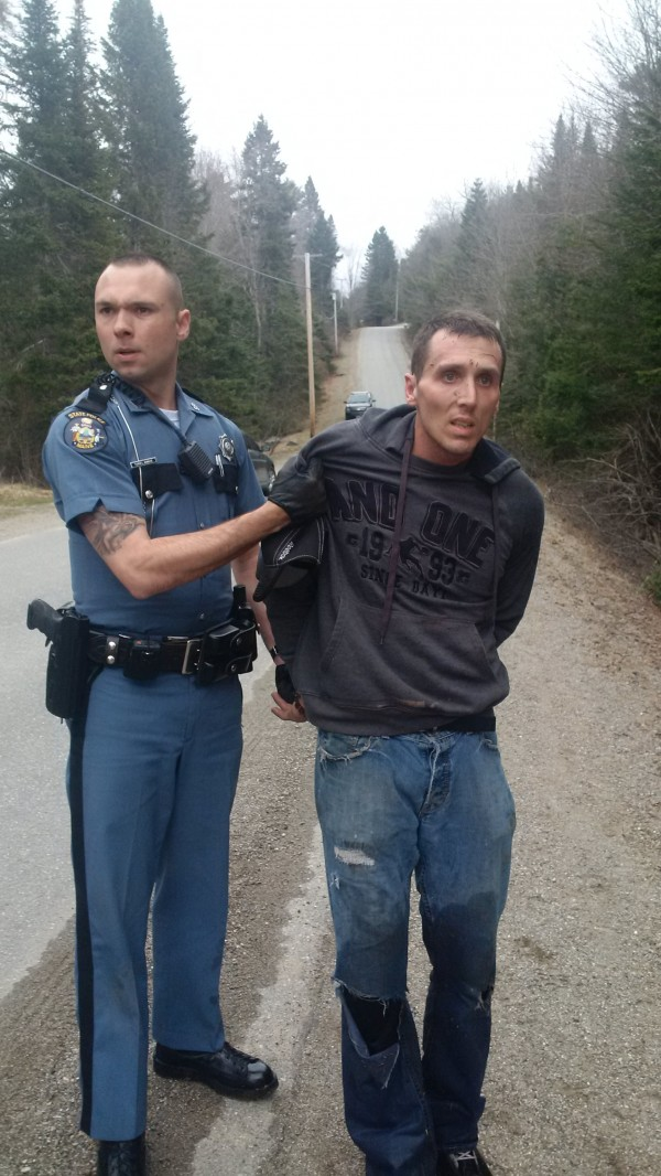 State Police Trooper Tucker Bonnevie takes Charles Fling, Jr., of Brewer, into custody in Dedham on Monday. Fling, suspected of burglary, led police on a high-speed pursuit through Dedham and Holden before crashing in Dedham.