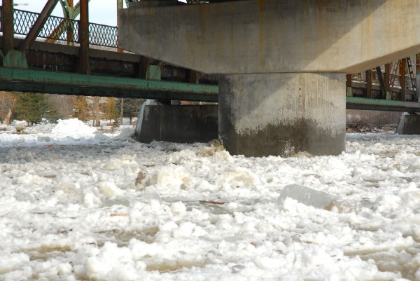Large chunks of ice hit against, but easily pass around the concrete piers of the old and new international bridges over the St. John River in Fort Kent.