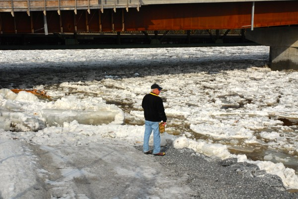 A resident watches the ice flow down the St. John River Friday morning in Fort Kent.