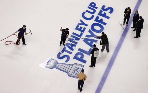 Members of the TD Garden staff paint on the Stanley Cup Playoffs logo after the Bruins clinched the best record in the NHL with a 4-1 win over the Buffalo Sabres Saturday in Boston.