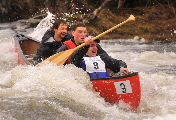 The crew of boat No. 9 reacts as they make it down the Six Mile Falls rapid during the 2013 Kenduskeag Stream Canoe Race.
