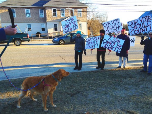 Scarborough resident Sean Flaherty's dog, Lily, joined two dozen protesters Tuesday night in opposing new ordinances for dogs on town beaches.