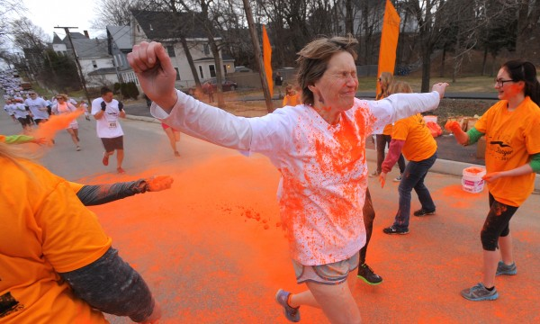 A runner makes her way through one of the color stations during the Color Bangor 5k run to raise money for the American Folk Festival. About 1700 runners and walkers completed the 5 kilometer race while being pelted with dyed starch along the way.