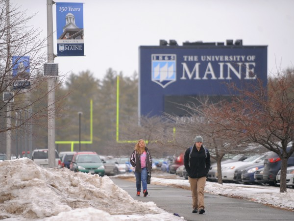 Students walk near the football field at the University of Maine in Orono on Monday.
