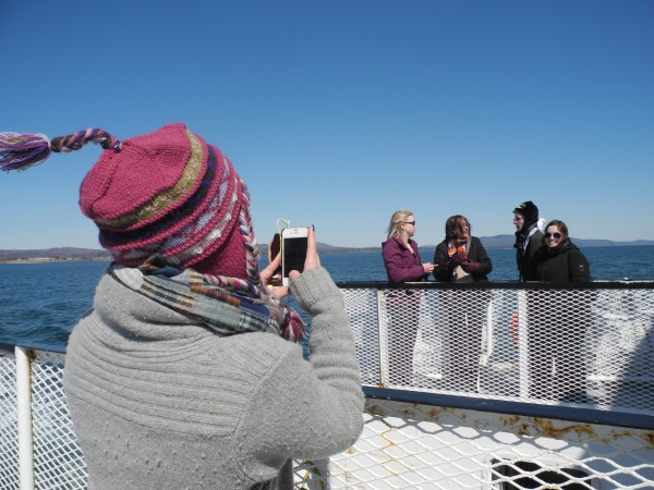 Christie Orcutt of Bangor snaps a photo of her bandmates Friday morning as the University of Maine Symphonic Band traveled on the ferry to Vinalhaven as part of its spring tour.