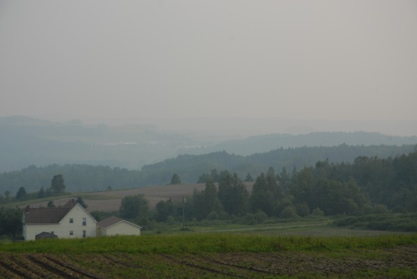 Smoke from forest fires in northwest Quebec in July created hazy conditions in northern Maine, obscuring hills looking westward over the St. John Valley.