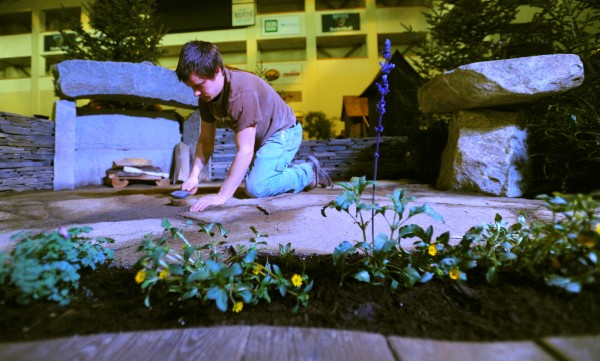 Michael Gelzinis puts the finishing touches on the diplay by the Newport-based Central Maine Stoneworks before the judging Thursday morning.  The BDN Maine Garden Show will open Friday at the Cross Insurance Center in Bangor.