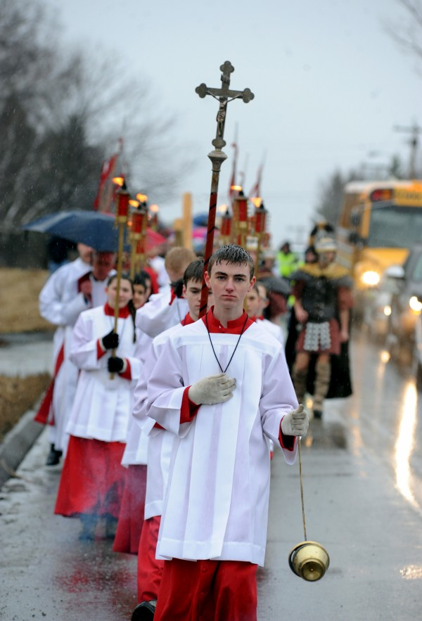 While swinging a thurible of incense, thurifer Jacob Gould leads the procession down North Main Street in Brewer during the third annual Way of the Cross Palm Sunday Community Procession. About 80 parishioners from St. Paul the Apostle Parish took part in the pilgrimage of prayer in preparation for Easter. The procession began at St. Joseph Catholic Church in Brewer and ended at St. John Catholic Church in Bangor.