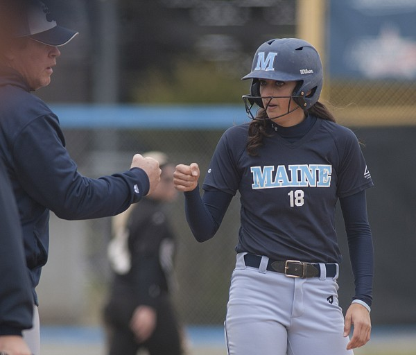 Maine's EmJ  Fogel (18) is congratulated by assistant coach Mike Coutts after reaching third in the second inning of their softball game against Binghamton in Orono on Saturday.