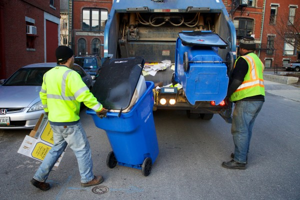 City workers Barry DeDomenico (left) and Kenneth Pringle feed the truck with large recycling containers from a multiunit building in Portland's Old Port on Wednesday. A new city ordinance requires landlords to provide a means of recycling to residents who live in multiunit apartment buildings.