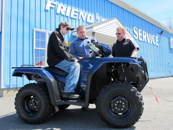 Brandon Trundy, 17, of Addison sits on an ATV Friday at Friend & Friend in Ellsworth while going over features of the vehicle with service technician Chance Curtis (center) and Alex Robinson, business development manager at the motorsports dealership. The ATV is a gift from Make-A-Wish Maine to Trundy, who has leukemia.