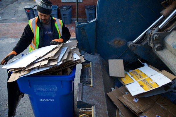 City worker Kenneth Pringle empties a large recycling bin Wednesday morning in Portland's Old Port.