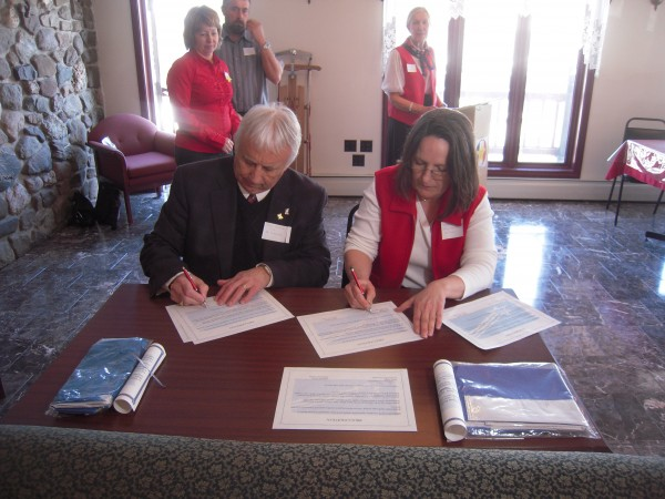 Carmel St. Amand, mayor of St. Leonard, N.B., and Nancy Troeger, acting town manager of Van Buren, sign certificates proclaiming the citizens of Pohenegamook and St. Athanase, Quebec, honorary citizens of Grande Riviere, the original settlement of Acadians that was bisected when the St. John River became the border between Canada and the U.S. in 1842. Looking on are  Louise LaBonte mayor of Pohenegamook, Andre St. Pierre, mayor of St. Athanase and Lydia Martin, CMA committee co-chair.