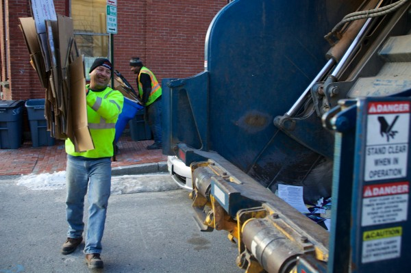 City workers Barry DeDomenico (left) and Kenneth Pringle put recycling from a multiunit building in the truck in Portland's Old Port Wednesday morning.
