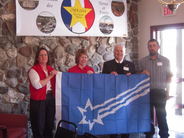 Town officials from Van Buren, Maine, and St. Leonard, N. B., (formerly the single town of Grande Rivier) present the flag of Grande Riviere to the mayors of Pohenegamook and St. Athanase, Quebec, in a ceremony April 9. From left, Nancy Troeger, acting town manager of Van Buren; Louise LaBonte, mayor of Pohenegamook; Carmel St. Amand, mayor of St. Leonard; and Andre St. Pierre, mayor of St. Athanase.