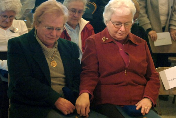 Patricia Schlegel (left) of Gray and Mary Andrews (right) of Solon comfort each other during the closing invocation at the Gold Star Honorable Service Medal ceremony Jan. 18, 2006, in the Hall of Flags in the State House in Augusta.  Cmdr. Robert A. Schlegel died on Sept. 11, 2001, in the terrorist attack on the Pentagon. Master Sgt. Evander E. Andrews died Oct. 10, 2001, while serving in the Air Force. Andrews was the first U.S. casualty in the post 9/11 wars.