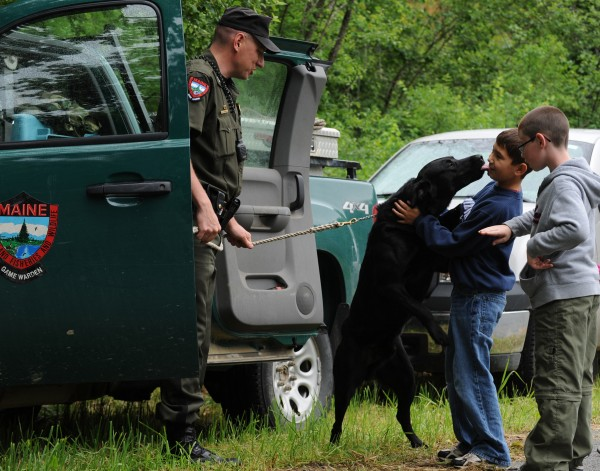 Koda, a black Lab, licks Deacon Lawless, second from right, of Fairfield, Texas on the face. Lawless and his cousin, Jayden Edwards, right, of Bangor were learning more about search and rescue dogs from Maine State Game Warden, Paul Farrington, left, on Saturday, June 20, 2009 at the Penobscot County Conservation Association's Outdoor Family Fun Day  in Brewer.