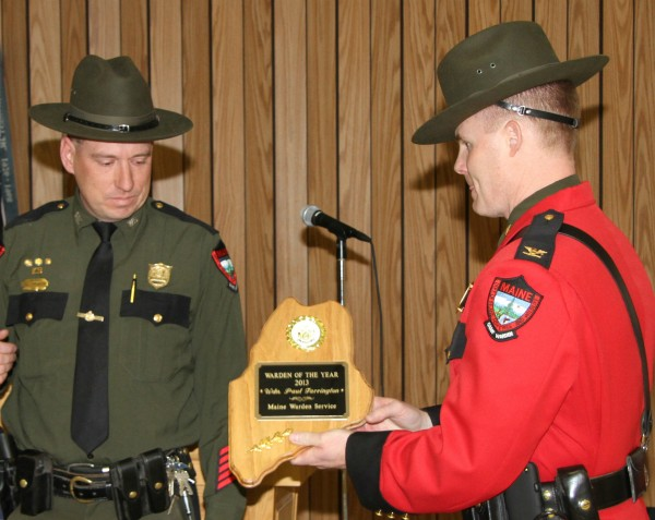 Paul Farrington of Springfield (left) accepts the 2013 Maine Game Warden of the Year award from Maine Warden Service Col. Joel Wilkinson at a banquet in Winslow on Wednesday, April 2, 2014.