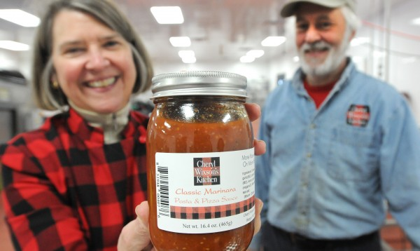 Cheryl Wixson (left) and her husband, Phillip McFarland, show off marinara sauce marketed under the name of Cheryl Wixson Kitchen at the Coastal Farms and Foods facility in Belfast in Jan. 2013.