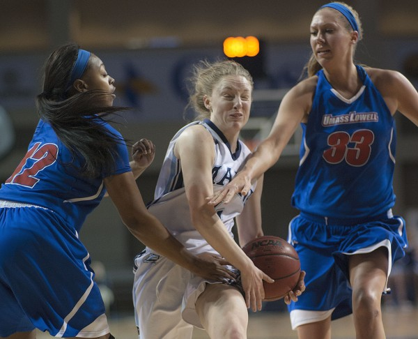 UMaine's Courtney Anderson (center) gets the double whack driving through the gauntlet of  UMass Lowell players Lindsey Doucette (right) and Asia Mitchell (left) in the first half of their game at the Cross Insurance Center in Bangor on Feb. 26.