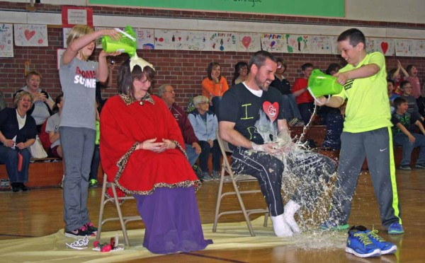 Anna Thibodeau, a student at Teague Park Elementary School in Caribou, carefully pours slime on the head of fifth-grade teacher Lorinda Duncan, dressed as Princess Duck, as Landon Thompson splashes slime onto the lap of Principal Steve Austin, dressed as Mr. Cool Duck. The costumes and sliming were part of a recent fundraising event at the school to benefit the American Heart Association.