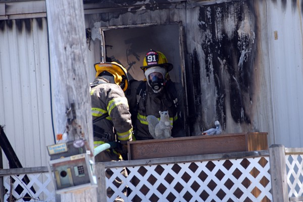 Lincoln firefighter Shannon Clifford (right) pauses during mop-up operations at a trailer fire on Loop Road in Chester on Thursday.
