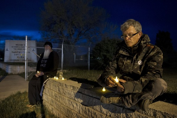 Army veterans David Bass (left) and Michael Clift participate in a candlelight vigil for the victims of the Fort Hood shooting at the East Gate of Fort Hood in Killeen, Texas, on Friday.