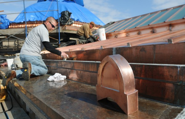 Last minute touches are applied prior to Thursday's unveiling of the new copper roof on the Bangor Public Library.
