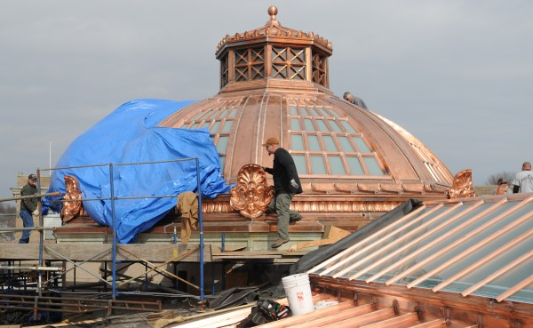 Workers remove a large blue tarp to reveal the new copper roof on the Bangor Public Library on Thursday