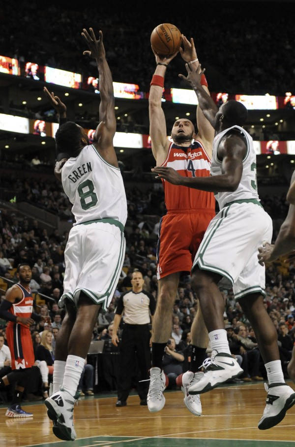 Washington Wizards center Marcin Gortat (4) shoots the ball past Boston Celtics forward Jeff Green (8) and Boston Celtics forward Brandon Bass (30) during the first half at TD Garden in Boston Wednesday night.