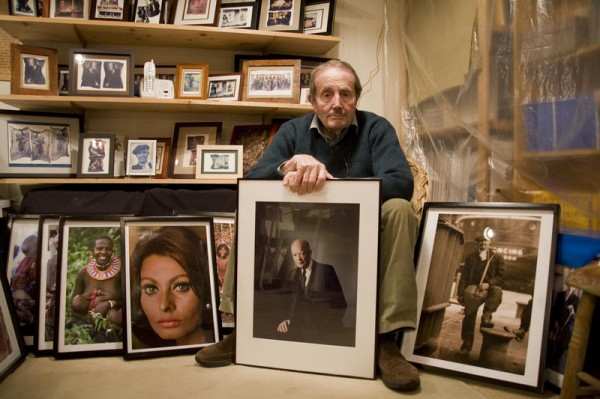 Robert Freson, a Belgium-born photojournalist who lives on Bailey Island, stands with some of his images. He is seeking a future home for his collection.