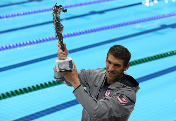 Michael Phelps shows off a special award he received from FINA for becoming the winningest Olympian in history at the 2012 Olympics at the Aquatic Center in London in this August 2012 file photo.