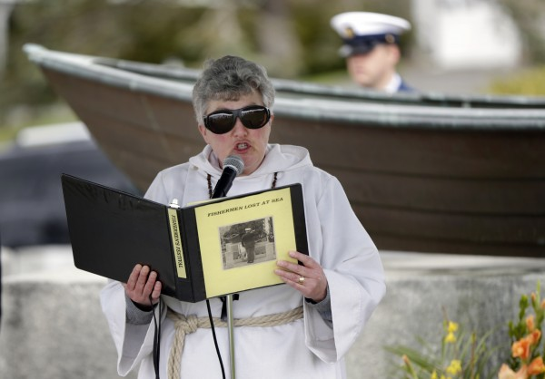 Ami Sawtelle, a pastor with the Boothbay Region United Methodist parish, reads the names of some of the local fishermen who perished at sea during a memorial service in Boothbay Harbor on Sunday.