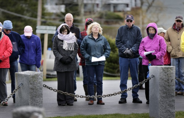 Men and women pause in remembrance of fishermen lost at sea during a memorial service in Boothbay Harbor on Sunday.