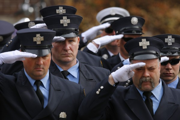 Firefighters salute during the funeral procession for Boston Fire Department Lt. Edward Walsh outside Saint Patrick's Church in Watertown, Mass., April 2, 2014.