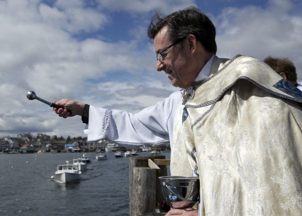 Rev. Frank J. Murray, pastor of All Saints parish, blesses commercial fishing boats at Boothbay Harbor on Sunday.