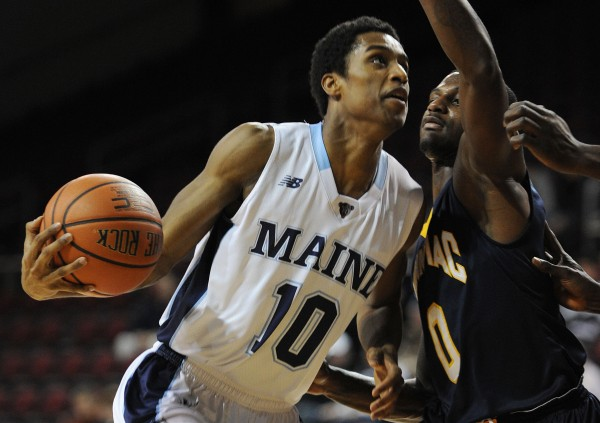 University of Maine guard Shaun Lawton (left) goes to the hoop against Quinnipiac's Umar Shannon at the Cross Insurance Center in Bangor in this November 2013 file photo. Lawton is transferring from the UMaine team.
