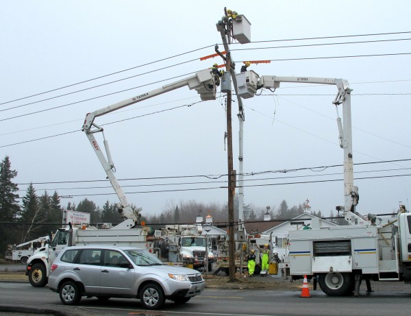 A car drives past where a Jeep crashed early Wednesday morning into a utility pole in Trenton as three workers with Emera Maine work to reconnect power lines to a new pole.