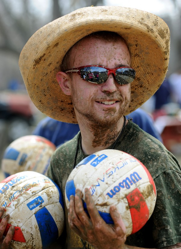 Alpha Delta sophomore Judson Walden, oozeball chairman, holds two muddy volleyballs during an oozeball game at the University of Maine on Wednesday.