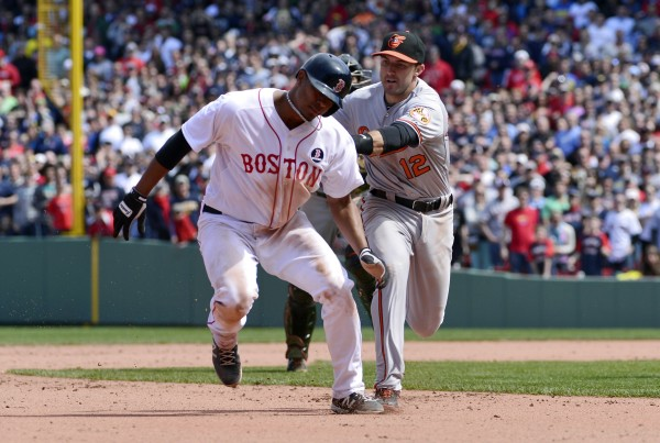 Boston Red Sox shortstop Xander Bogaerts (2) gets tagged out by Baltimore Orioles third baseman Ryan Flaherty (3) to end the eighth inning at Fenway Park.