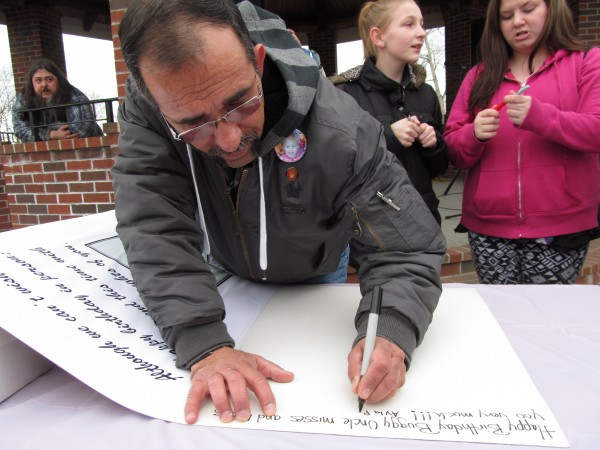 Ronald Reynolds, the maternal grandfather of missing toddler Ayla Reynolds, signs a giant fourth birthday card for the girl during a Friday night vigil. Ayla disappeared from her father's home in Waterville in December 2011.