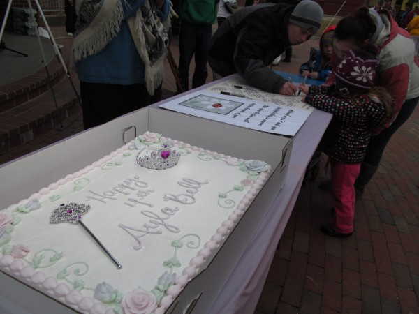 A princess-themed fourth birthday cake is displayed while friends and family of missing toddler Ayla Reynolds sign a giant card for the girl Friday night during a vigil in Biddeford. Attendees released balloons and lit candles in memory of Ayla, who has never been found, but police believe fell victim to foul play at the age of 20 months old in December 2011.
