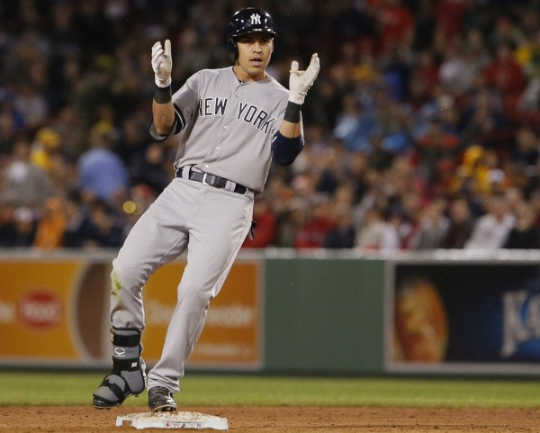 Jacoby Ellsbury (22) of the New York Yankees reacts after hitting a double two-run double against his former team in the fifth inning of Tuesday night's game at Fenway Park in Boston. The Yankees won 9-3.
