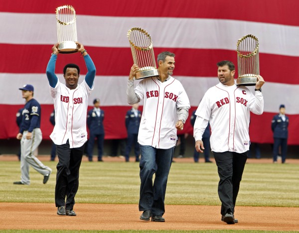 Former Boston Red Sox players Pedro Martinez , Mike Lowell and Jason Varitek carry out World Series trophies during pre-game ceremonies before the game against the Milwaukee Brewers at Fenway Park on Friday.