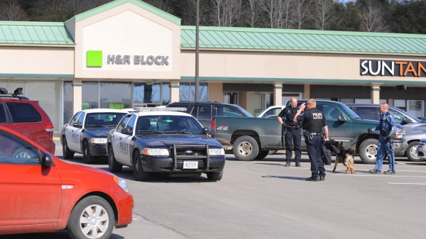 Police search a mall parking lot as they investigating a robbery that happened at the Maine Savings Federal Credit Union on Broadway in Bangor Thursday.