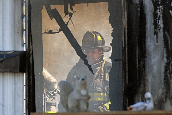 Lincoln firefighters conduct mop-up operations at a fire in Chester on Thursday.
