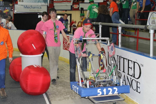 Old Town High School robotics team member Cameron Sullivan (right) pushes the 23-member team's robot out on the field during the Pine Tree Regional Competition on April 4 at the Androscoggin Bank Colisee in Lewiston. Behind Sullivan are driver Zach Fox and coach Austin Comeau.