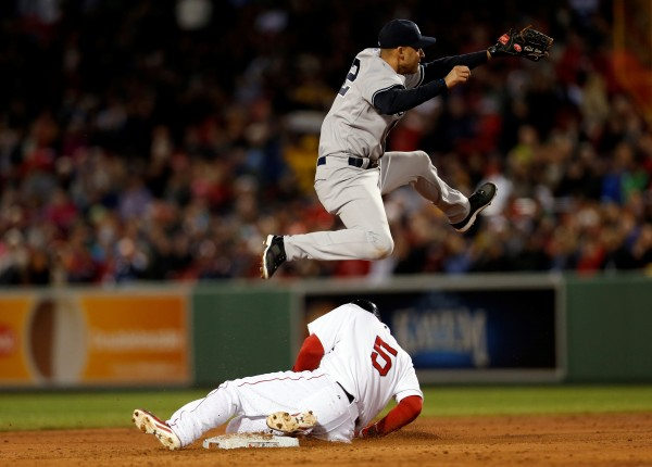 New York Yankees shortstop Derek Jeter (2) leaps over Boston's Jonny Gomes (5) but fails to turn the double play during the second inning of Thursday night's gamme at Fenway Park in Boston. The Yankees won 14-5.