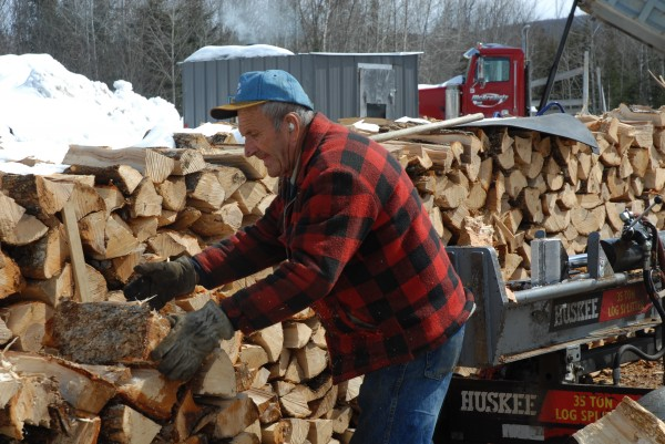 Yard worker Gerard Thibodeau uses a mechanized splitter to prepare a load of wood for delivery. Firewood is in scare supply in northern Maine and dealers including Robert McBreairty in Fort Kent are doing their best to keep up with demand.